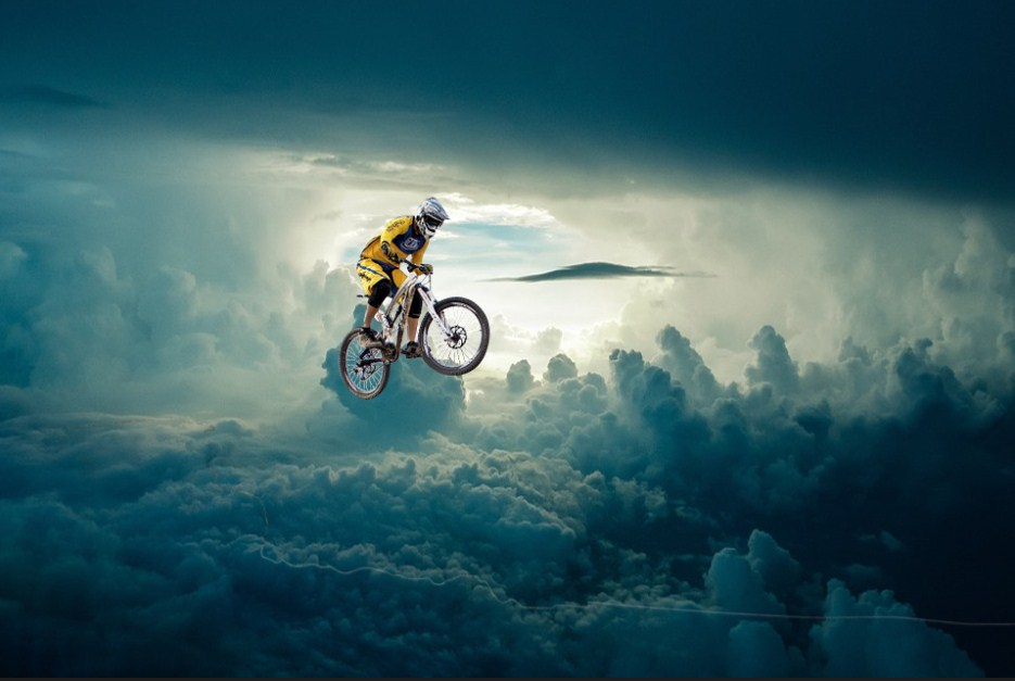 A man on bicycle floating in the mid in cloudy bachdrop