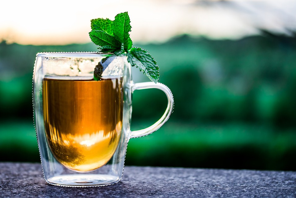 A cup of tea with basil on top